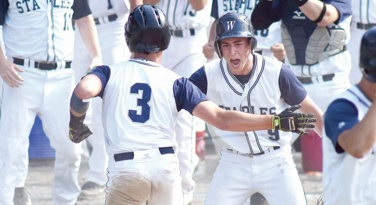 Hour photo/John Nash - Staples High School's Zach Azadian, right, greets teammate Michael Cusa (3) after Cusa scored a run in the Wreckers' 11-0 Class LL semifinal win over Norwalk at Muzzy Field in Bristol.