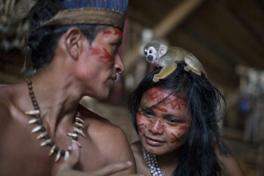 A small monkey sits atop the head of a woman in the Tatuyo indigenous community near Manaus, Brazil, Monday, May 19, 2014. Manaus is one of the host cities for the 2014 World Cup in Brazil. (AP Photo/Felipe Dana)