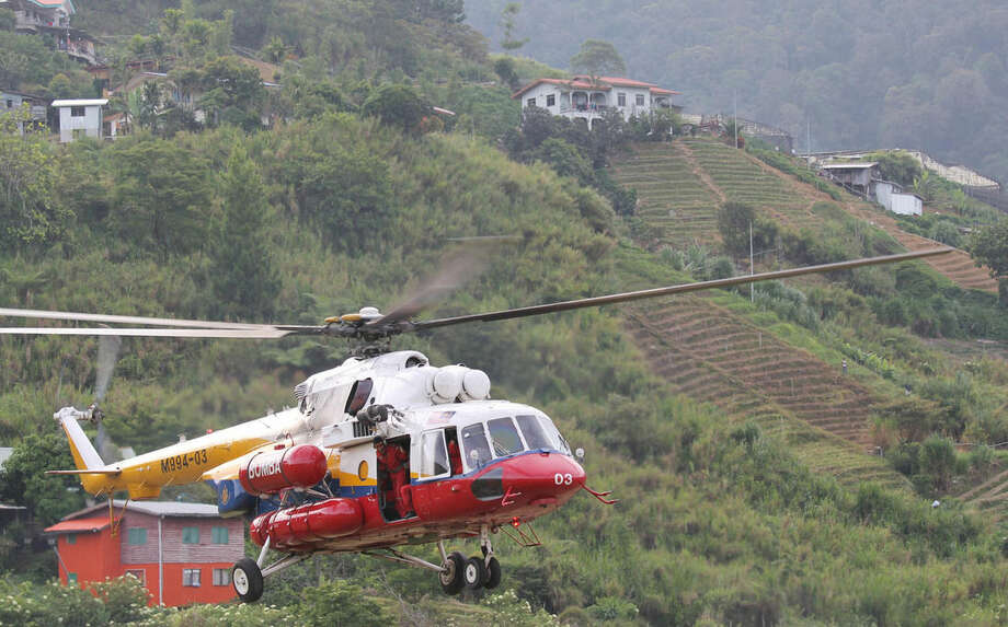 Munehiro Yamaoka/Kyodo News via APA helicopter leaves Kundasang, Malaysia for Mount Kinabalu to recover the bodies of climbers Saturday, June 6, 2015. Rescuers on Saturday recovered the bodies of several more climbers from Malaysia's highest peak a day after it was struck by a strong earthquake.