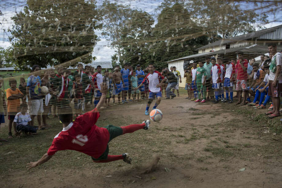 People watch as a goalkeeper fails to stop a penalty kick during a soccer tournament in Sao Pedro community, near Manaus, Brazil, Sunday, May 18, 2014. Manaus is one of the host cities for the 2014 World Cup in Brazil. (AP Photo/Felipe Dana)