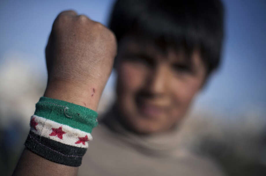 In Saturday, April 5, 2014 photo, Ahmed Mahmoud, 12, shows his wrist band with colors of the Syrian revolution flag, near his family's makeshift tent in an unofficial Syrian refugee camp on the outskirts of Amman, Jordan. For Ahmed, school is a distant memory. He helps his father sell vegetables in a wholesale market near their camp where he has lived the past year.(AP Photo/Khalil Hamra)