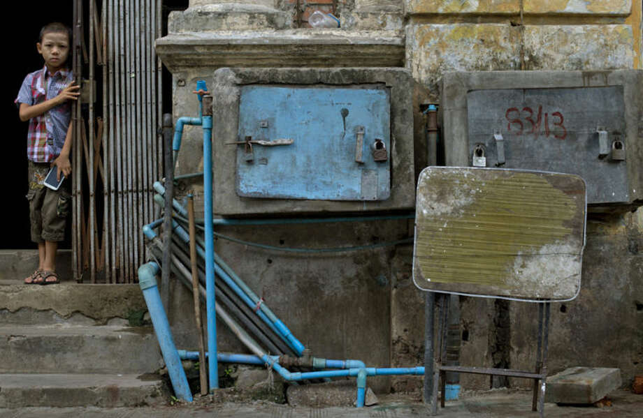 A boy peeks out from an old apartment building, in which water pumps are boxed and padlocked for protection in downtown Yangon, Myanmar, Tuesday, May 20, 2014. (AP Photo/Gemunu Amarasinghe)