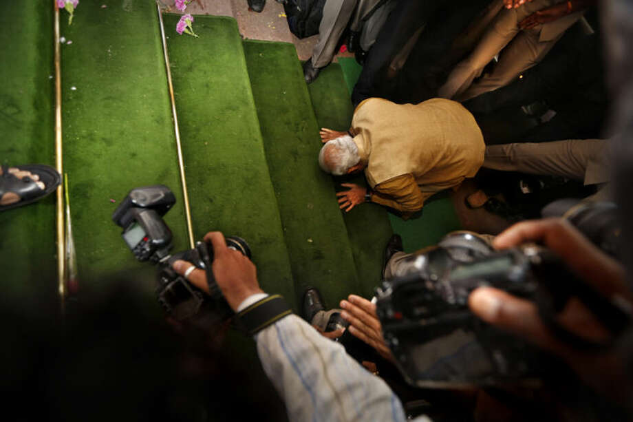 India's next prime minister and Hindu nationalist Bharatiya Janata Party (BJP) leader Narendra Modi, bends down on his knees on the steps of the Indian parliament building as a sign of respect as he arrives for the BJP parliamentary party meeting in New Delhi, India, Tuesday, May 20, 2014. The BJP has started putting together a new government by formally choosing Modi to be the country's next prime minister following a resounding victory in national elections. (AP Photo/Manish Swarup)