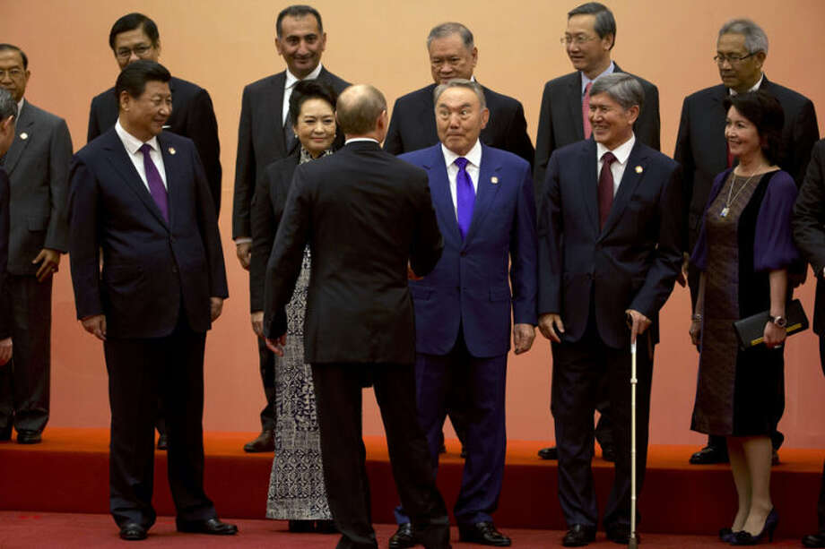 Kazakhstan's President Nursultan Nazarbayev, front row third right, reacts to a handshake greeting by Russian President Vladimir Putin, third left, as Chinese President Xi Jinping, left, and Chinese first lady Peng Liyuan, second left, look on with other leaders during a group photo session for the fourth summit of the Conference on Interaction and Confidence Building Measures in Asia (CICA) in Shanghai, China, Tuesday, May 20, 2014. Putin met with Xi in a diplomatic boost for the isolated Russian leader but the two sides had yet to agree on a widely anticipated multibillion-dollar natural gas sale. (AP Photo/Ng Han Guan, Pool)