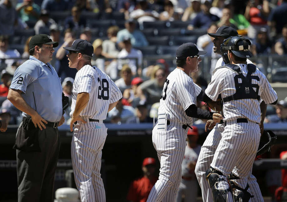 Teammates hold back New York Yankees starting pitcher CC Sabathia, right, as manager Joe Girardi, second from left, argues with umpire Dan Bellino, left, during the sixth inning of a baseball game against the Los Angeles Angels at Yankee Stadium, Sunday, June 7, 2015 in New York. Both Sabathia and Girardi were ejected from the game. (AP Photo/Seth Wenig)