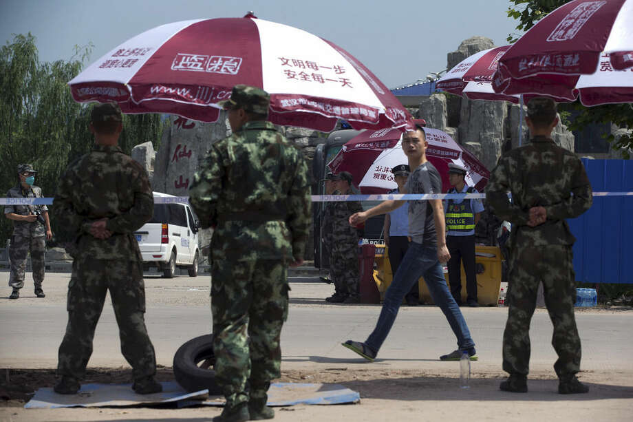 In this Saturday, June 6, 2015 photo, a man walks past policemen and soldiers stand guard outside the closed off mortuary where bodies of passengers aboard the capsized Eastern Star cruise ship are taken, in Jianli county of southern China's Hubei province. As the closest town to the site of Monday's Yangtze River cruise ship disaster, Jianli is the staging area for what began as a rescue effort, but which has now shifted to identifying the remains of the more than 430 people killed when the ship capsized in a freak tornado. Just 14 people survived in what is now officially China's worst maritime disaster in nearly seven decades. (AP Photo/Andy Wong)