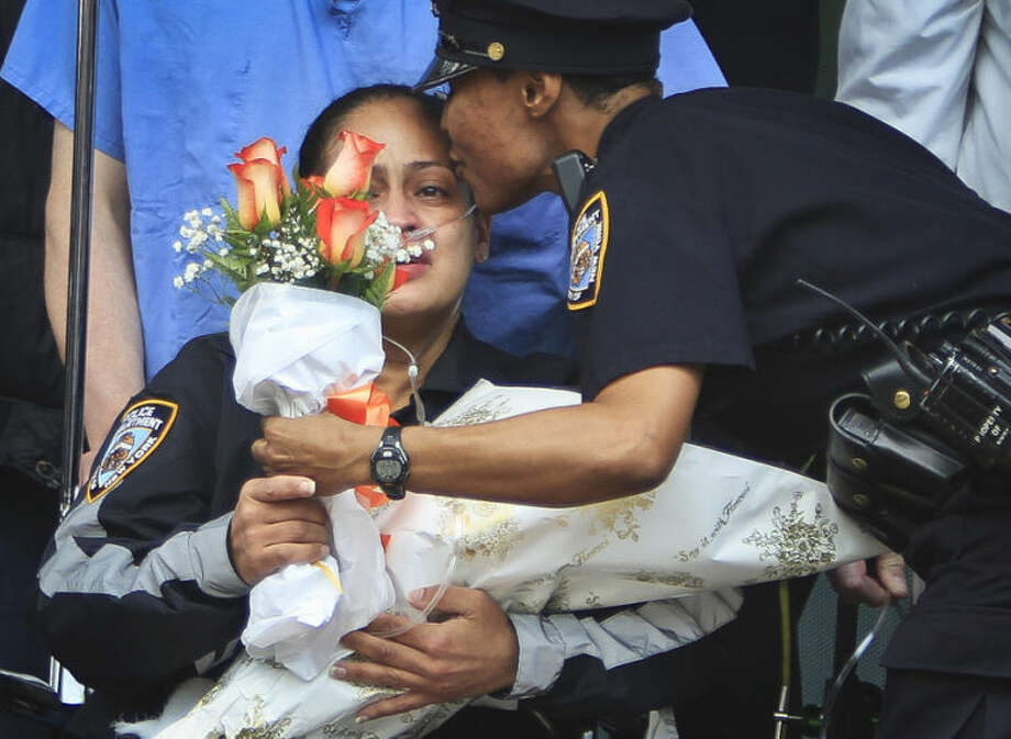 New York Police Department Officer Rosa Rodriguez, left, receives flowers and a kiss from a police officer as she leaves Weill Cornell Medical Center, Monday May 19, 2014, in New York. Rodriguez was severely injured while responding to a fire which killed her partner. The officers were overcome by smoke at a Coney Island housing project. (AP Photo/Bebeto Matthews)