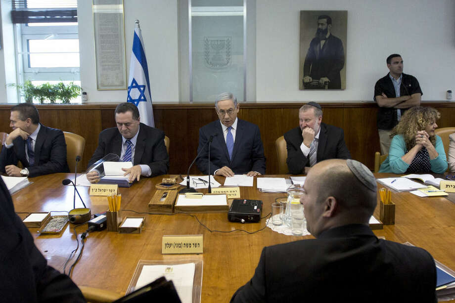 Israeli Prime Minister Benjamin Netanyahu, center, attends the weekly cabinet meeting in his Jerusalem office, Sunday, June 7, 2015. Israel's prime minister has slammed the international community for its silence over recent rocket attacks from Gaza — while warning that a strong reprisal is forthcoming. (AP Photo/Sebastian Scheiner, Pool)