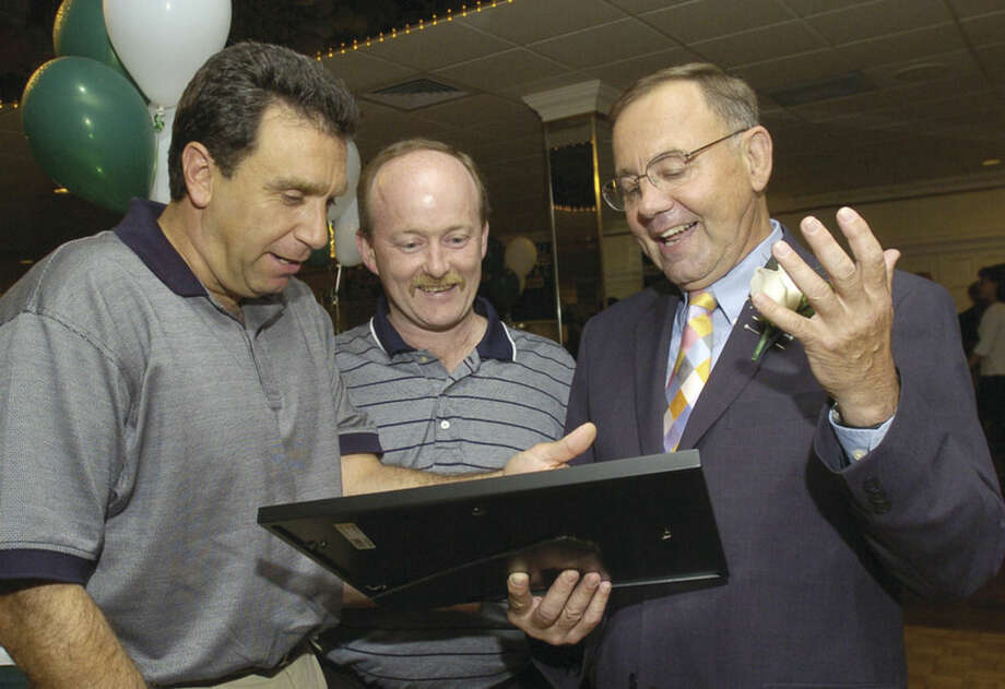 Former Norwalk High softball coach Ray Barry, right, reacts as he receives a photo of the JV baseball team he coached at Central Catholic from former players Joe Gallo and Sal Trombetta at Barry's retirement dinner Wednesday at Continental Manor. Barry started his career at Central Catholic.photo