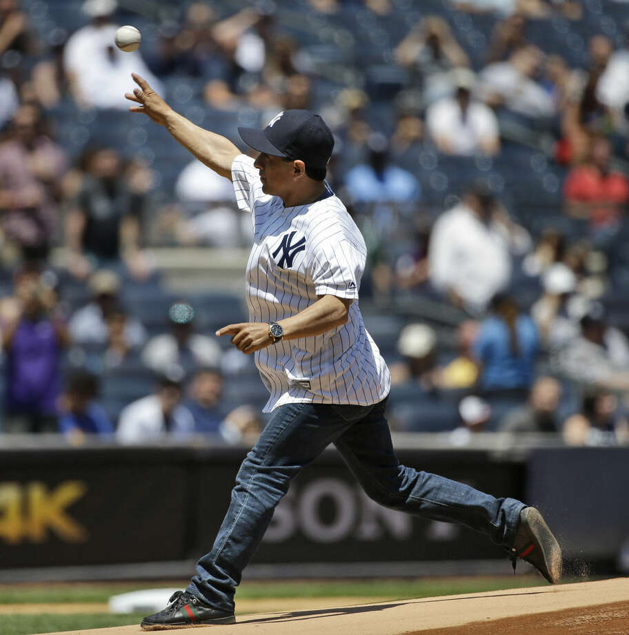 Triple Crown-winning jockey Victor Espinoza throws out the ceremonial first pitch before a baseball game between the New York Yankees and the Los Angeles Angels, Sunday, June 7, 2015, in New York. (AP Photo/Seth Wenig)
