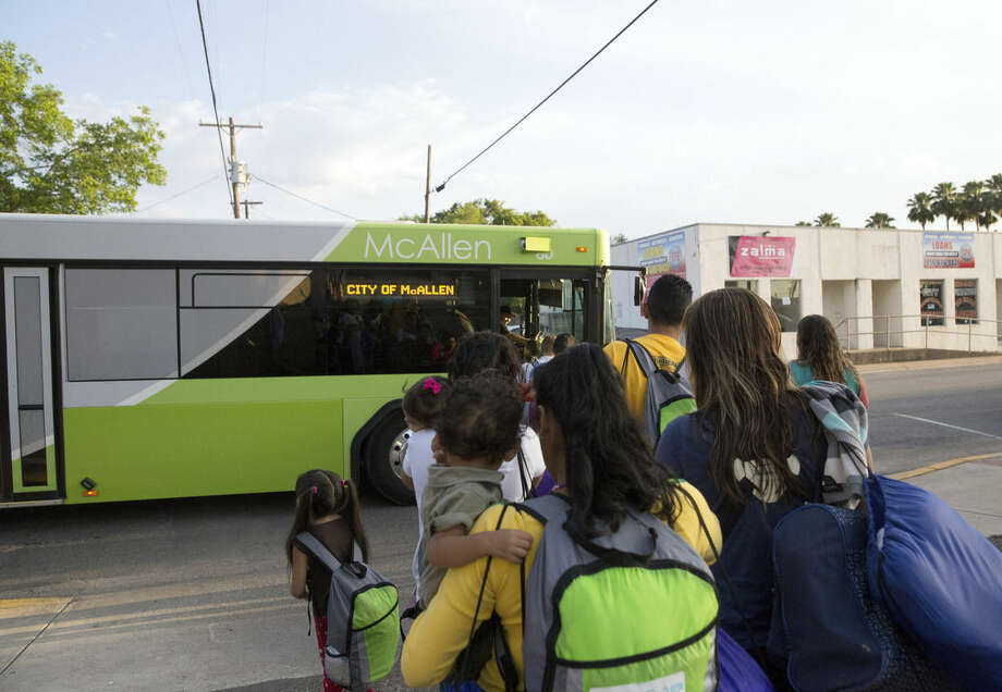 In this April 30, 2105 photo, immigrant families, many of them mothers with children, board a bus headed to the downtown bus station in McAllen, Texas. The immigrants, mostly from Central America, had crossed the Rio Grande and were later released by Border Patrol with notices to appear before immigration judges around the country. (AP Photo/Seth Robbins)