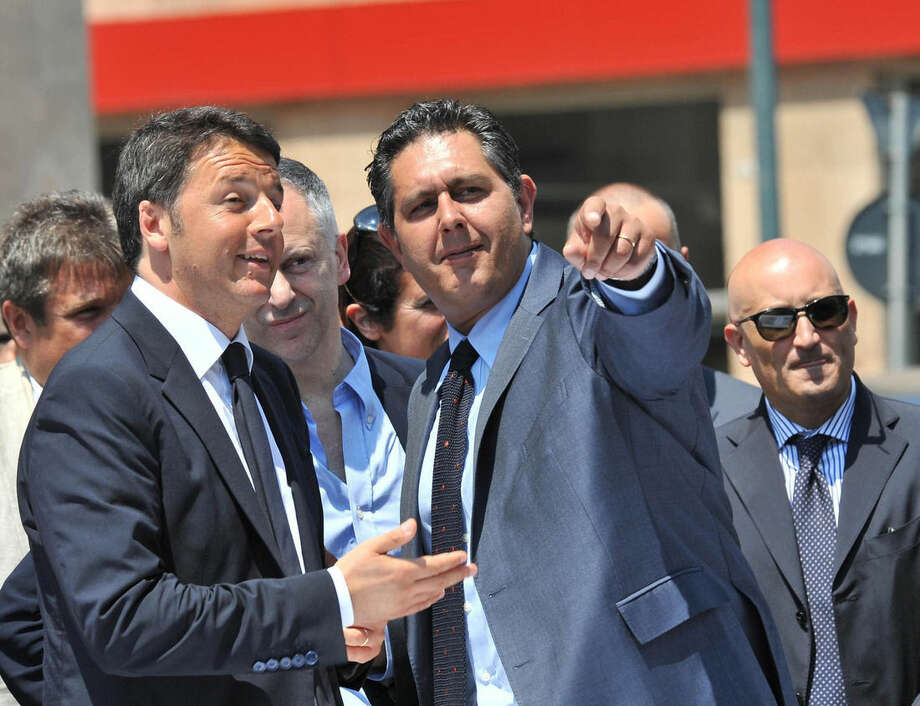 In this picture taken on June 6, 2015 and made available on Sunday, June 7, 2015, Italian premier Matteo Renzi, left, shares a word with Liguria Governor Giovanni Toti, center, in Genoa, Italy. Giovanni Toti, elected just last week, was among the northern Italian politicians vowing to refuse to host any more migrants while asylum requests are being evaluated. (Paolo Zeggio/ANSA via AP)