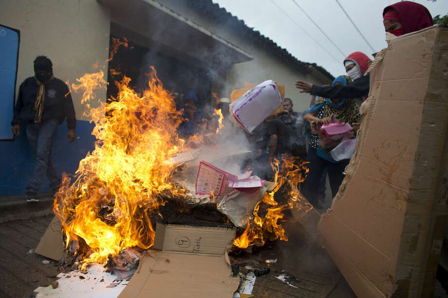 Masked citizens and parents of missing students from Ayotzinapa burn ballots and other voting materials taken from a polling station, in Tixtla, Guerrero State, Mexico, Sunday, June 7, 2015. Security forces were not present in Tixtla, where an anti-election group burned all materials from multiple polling stations before clashing with another group of town residents determined to defend a polling place. (AP Photo/Rebecca Blackwell)