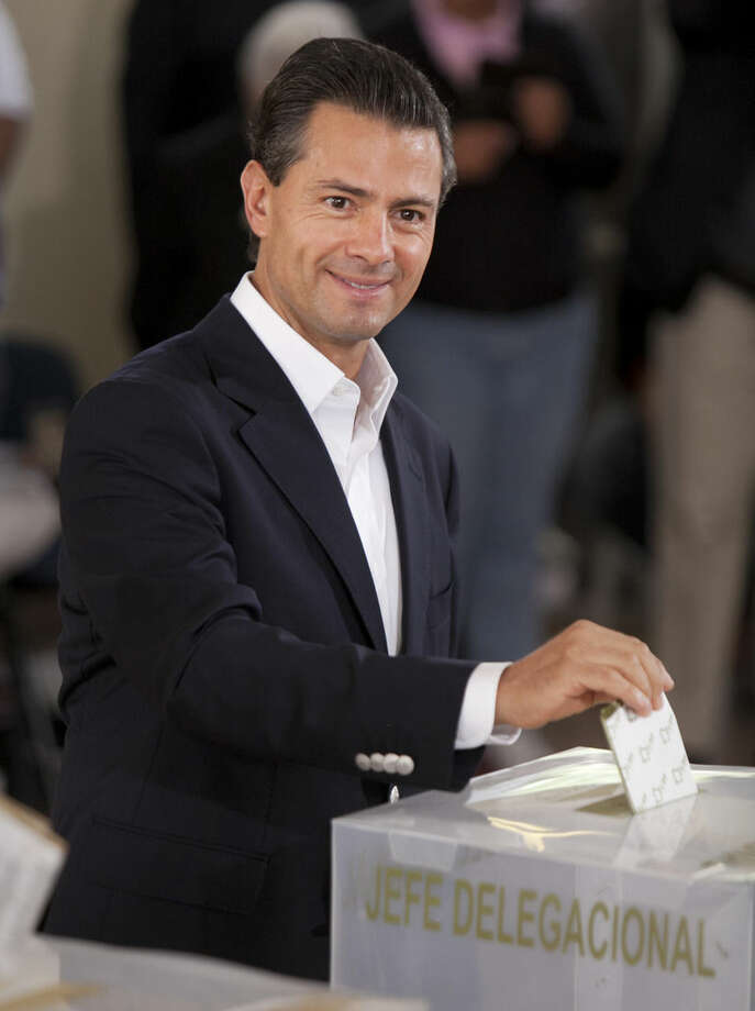 "Mexico's President Enrique Pena Nieto cast his vote during the country's midterm elections in Mexico City, Sunday, June 7, 2015. Protesters burned ballot boxes in several restive states of southern Mexico on Sunday in an attempt to disrupt elections seen as a litmus test for President Pena Nieto's government, while officials said the vote was proceeding satisfactorily despite ""isolated incidents."" (AP Photo/Marco Ugarte)"