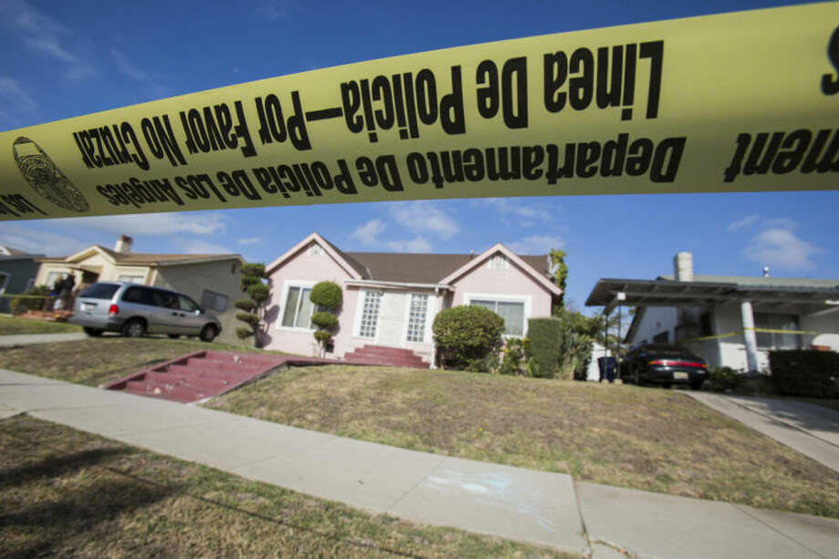 """Yellow police tape seals off the home of actor Michael Jace on Tuesday, May 20, 2014, in Los Angeles. Jace, who played a police officer on the hit TV show """"The Shield,"""" was arrested on suspicion of homicide after his wife was found shot to death in their Los Angeles home, authorities said. Police arrived at the couple's home around 8:30 p.m. Monday after a report of shots fired, Officer Chris No said. April Jace, 40, was found dead inside, officials said. Jace was taken into custody and booked early Tuesday on suspicion of homicide, No said. He was being held in a Los Angeles jail in lieu of $1 million bail. (AP Photo/Ringo H.W. Chiu)"""