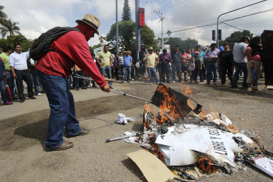 Teachers belonging to a dissident union burn ballot boxes and ballots in the city of Oaxaca, Mexico, Sunday, June 7, 2015. Midterm elections usually draw light turnout, but attention was unusually high this time as a loose coalition of radical teachers' unions and activists vowed to block the vote for 500 seats in the lower house of Congress, nine of 31 governorships and hundreds of mayors and local officials. (AP Photo/Luis Alberto Hernandez)