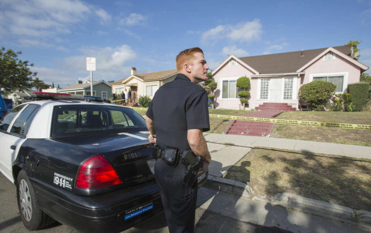 A police officer stands guard in front of the home of actor Michael Jace on Tuesday, May 20, 2014, in Los Angeles. Jace, who played a police officer on the hit TV show