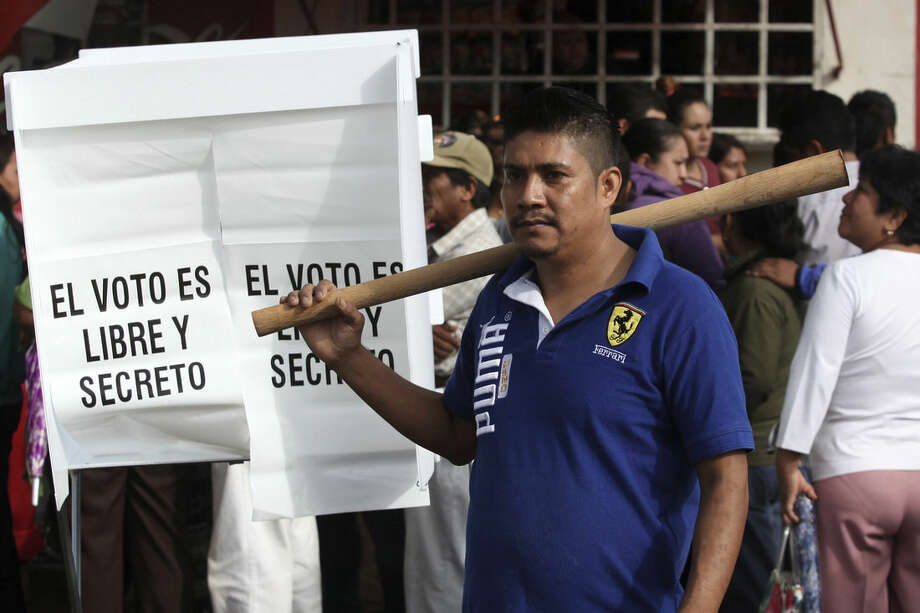 A man armed with a large wooden stick guards a polling station in the town of Tixtla, Mexico, Sunday, June 7, 2015. A anti-election group, accompanied by parents of the 43 missing students from Ayotzinapa, burned all election materials from several polling stations before blocked from accessing one polling station by another group of town residents. (AP Photo/Felix Marquez)