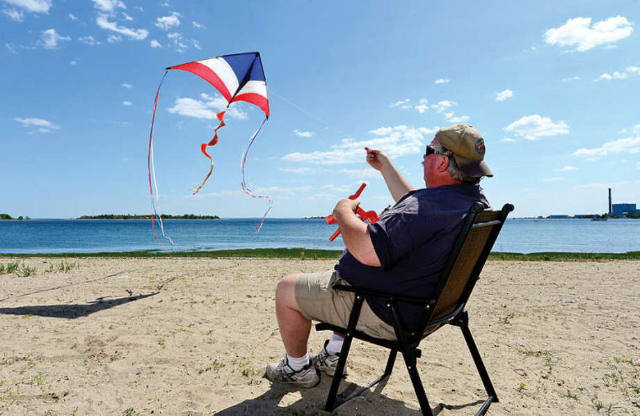 Hour photo / Erik Trautmann Norwalk resident Kevin Grady flies a kite on a beautiful, breezy day at Calf Pasture Beach Tuesday.