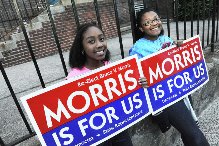 Briana McFarlane 12 and Asia Johnson 11 help the cause for Bruce Morris Tuesday at Columbus School. Hour photo/Matthew Vinci