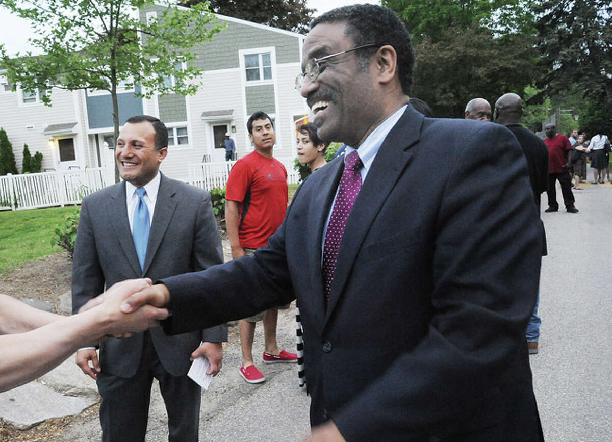 Norwalk Democrats hold a caucus at Columbus Magnet School, to choose between Bruce V. Morris and Warren A. Pena to run as endorsed candidate for 140th District seat in state House of Representatives. Warren Pena left and Bruce Morris on the right greet voters. Hour photo/Matthew Vinci