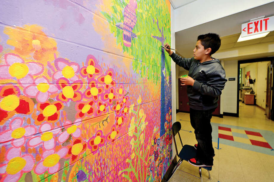 Hour photo / Erik Trautmann Silvermine Elementary School's graduating 5th grade students including Brandon Mora complete a 20 foot mural project in conjunction with the Silvermine Arts Guild Tuesday. The mural program, in its 13th year, involves all the 5th grade students and requires collaboration, research and creativity in executing the final mural project.