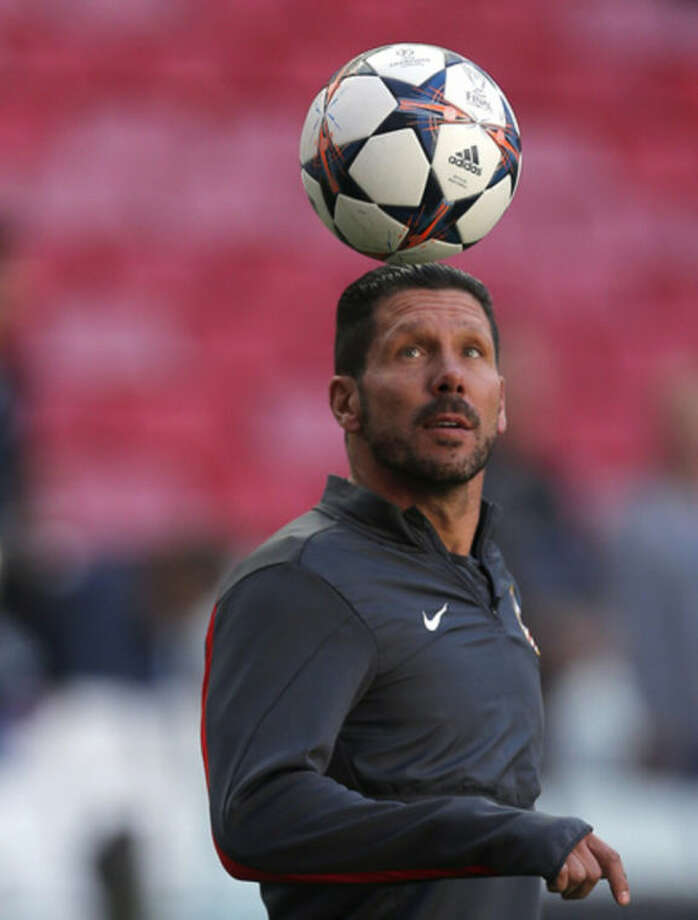 Atletico's coach Diego Simeone heads the ball, during a training session ahead of Saturday's Champions League final soccer match between Real Madrid and Atletico Madrid, in Luz stadium in Lisbon, Portugal, Friday, May 23, 2014. (AP Photo/Andres Kudacki)