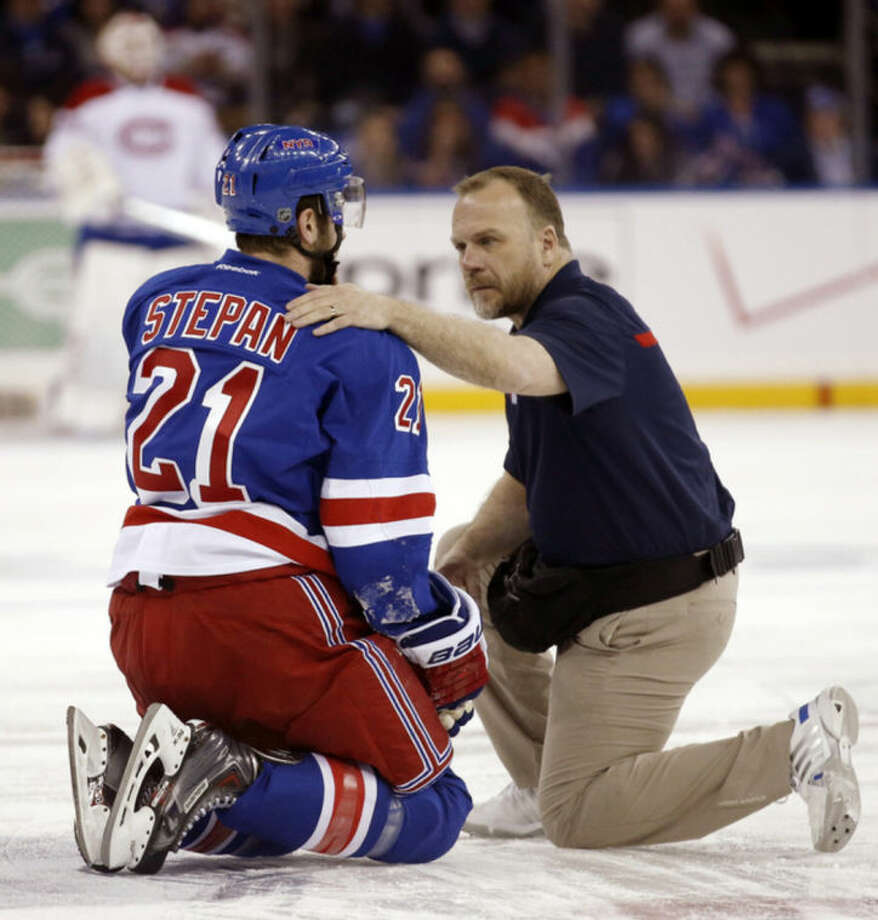 In this May 22, 2014 photo, a staff member examines New York Rangers center Derek Stepan (21) after Stepan took a hit from Montreal Canadiens forward Brandon Prust during the first period of Game 3 of the NHL hockey Stanley Cup playoffs Eastern Conference finals in New York. Stepan has a broken jaw and is undergoing surgery. Rangers coach Alain Vigneault made the surprising announcement Friday, May 23, 2014, on the first of two off days in the series New York leads 2-1. Prust wasn't penalized in the first period of Montreal's 3-2 overtime win Thursday night, but he faces an NHL hearing Friday and a possible suspension. (AP Photo/Kathy Willens)
