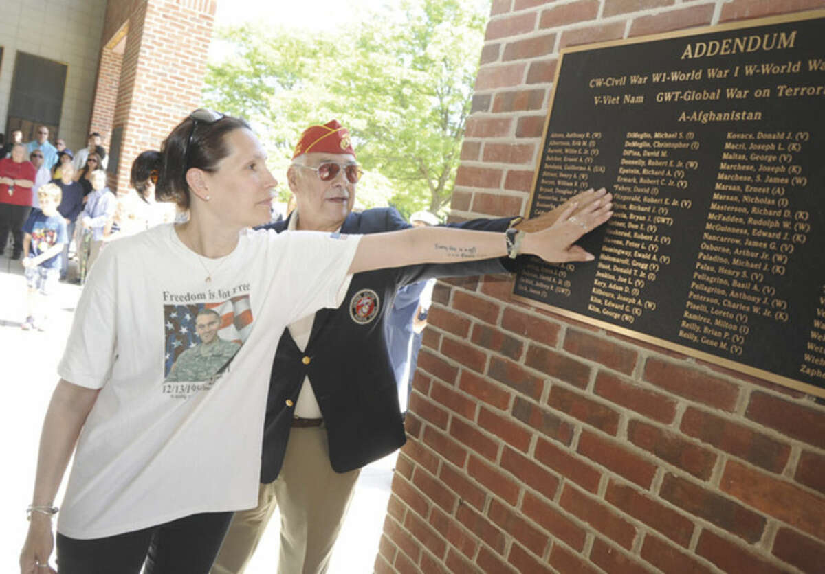 Hour photo/Matthew Vinci Caroline Ettinger, aunt of David Fahey, the Norwalker who was killed Feb. 28, 2011, while serving as a U.S. Army military policeman in Afghanistan, is shown with Dan Caporale, chairman of the Veterans Memorial committee on Sunday as they unveil the addendum plaque at Norwalk City Hall Veterans Wall of Fame.