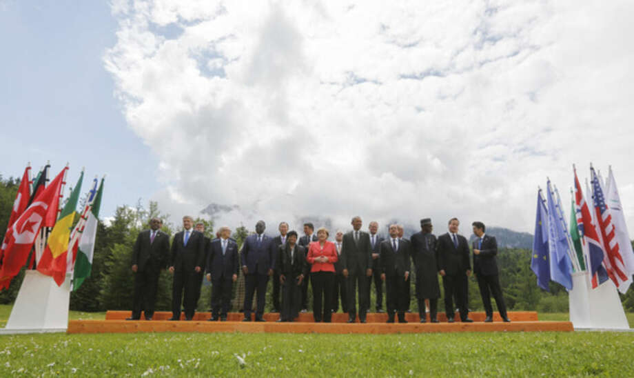 German Chancellor Angela Merkel, center left, speaks with U.S. President Barack Obama, center right, during a group photo of G-7 leaders and Outreach guests at the G-7 summit at Schloss Elmau hotel near Garmisch-Partenkirchen, southern Germany, Monday, June 8, 2015. G-7 leaders, in a second and final day of the conference, were set to tackle the difficult issue of climate change and fighting terrorism. Front row left to right, Ethiopian President Hailemariam Desalegn, Canadian Prime Minister Stephen Harper, Tunisian President Beji Caid Essebsi, Senegal President Macky Sall, Liberian President Ellen Johnson Sirleaf, French President Francois Hollande, Nigerian President Muhammadu Buhari, British Prime Minister David Cameron, Japanese Prime Minister Shinzo Abe. (AP Photo/Markus Schreiber)