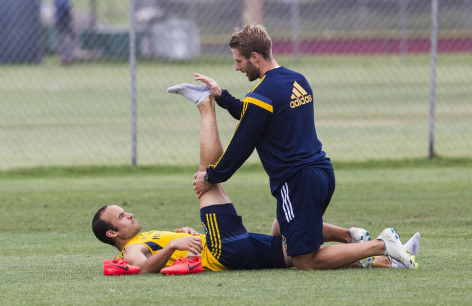 Los Angeles Galaxy forward Landon Donovan is assisted in stretching by trainer Kurt Andrews during a training session at StubHub Center in Carson, Calif., Saturday, May 24, 2014. Donovan, the most accomplished American player in the history of men's soccer, won't be going to his fourth World Cup. The 32-year-old attacker was among seven players cut Thursday when coach Jurgen Klinsmann got down to the 23-man limit well before the June 2 deadline. (AP Photo/Ringo H.W. Chiu)