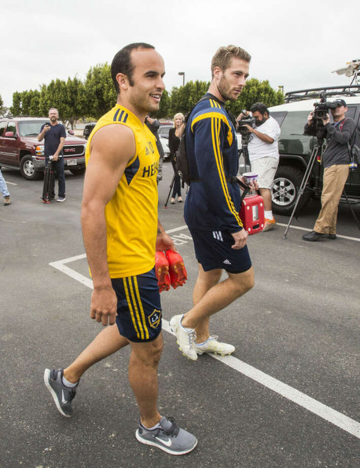 Los Angelese Galaxy forward Landon Donovan, left, arrives for a training session at StubHub Center in Carson, Calif., Saturday, May 24, 2014. Donovan, the most accomplished American player in the history of men's soccer, won't be going to his fourth World Cup. The 32-year-old attacker was among seven players cut Thursday when coach Jurgen Klinsmann got down to the 23-man limit well before the June 2 deadline. (AP Photo/Ringo H.W. Chiu)