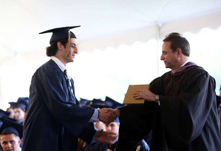 Adam Harrison Byer recieves his diploma during Weston High School's annual commencement ceremony Friday evening. Hour Photo / Danielle Calloway