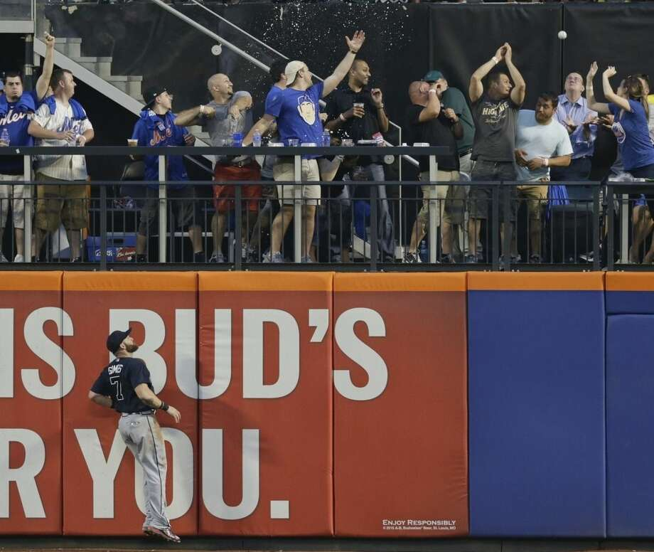 Atlanta Braves' Jonny Gomes (7) chases a ball hit by New York Mets' John Mayberry Jr. for a two-run home run during the fourth inning of a baseball game Friday, June 12, 2015, in New York. (AP Photo/Frank Franklin II)