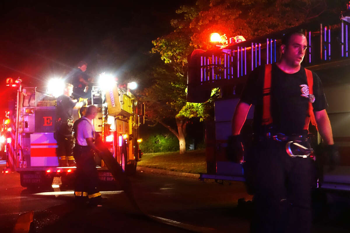 Hour photo/Jeff Dale Firefighters clean up the scene at 8 Lighthouse Lane in Norwalk Friday night after a house fire displaced a family of three and their pet bulldog Rex.