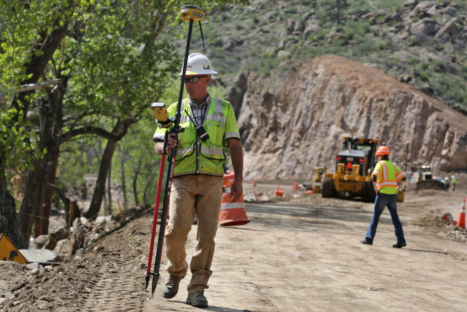 In this May 20, 2014 photo, American Civil Constructor's Jim Overlin uses a GPS tool to check exact height consistency along what will eventually be an improved mountain highway, during a road-building operation on Highway 36 between Lyons at Estes Park, Colorado. The goal of the project is to move the road further from the adjacent river, which undermined the road for miles during floods the previous fall, in hopes of preventing such destructive flooding in the future. (AP Photo/Brennan Linsley)