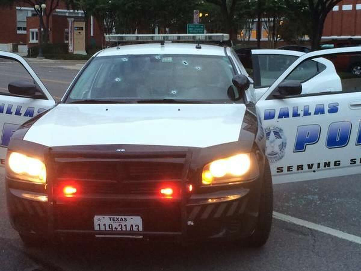 This photo sent via Twitter by the Dallas Police Department shows gunshot damage to a squad car Saturday, June 13, 2015, in Dallas. Police Chief David Brown says a police sniper has shot the suspect in an overnight attack on police headquarters and that the department is checking to see if he's still alive. Brown says investigators believe the man acted alone in the early-morning attack on Dallas police headquarters, despite early witness reports that others may have taken part. (Dallas Police Department, via AP)