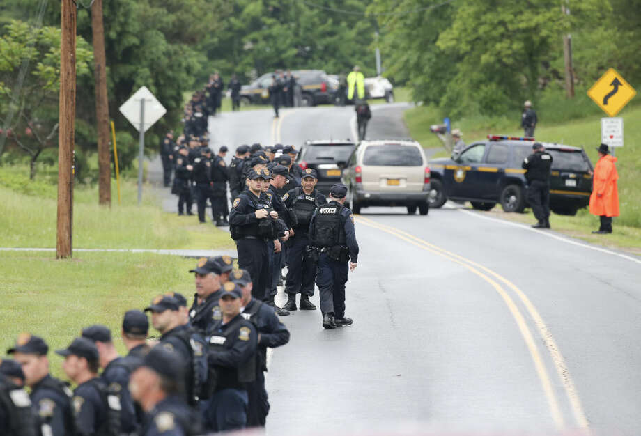 Law enforcement officers walk along Trudeau Road at Route 3 and after emerging from the woods during a search for two escapees from Clinton Correctional Facility on Friday, June 12, 2015, near Dannemora, N.Y. Squads of law enforcement officers are searching for David Sweat and Richard Matt, two murderers who escaped from the maximum-security prison in northern New York. (AP Photo/Mike Groll)