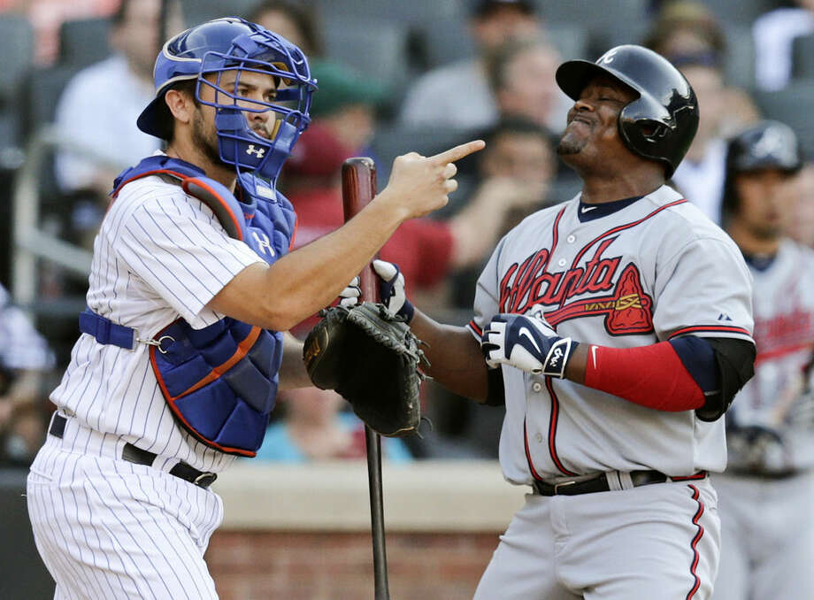 Atlanta Braves' Juan Uribe (2) and New York Mets catcher Travis d'Arnaud (7) react after Uribe struck out during the ninth inning of a baseball game Saturday, June 13, 2015, in New York. (AP Photo/Frank Franklin II)