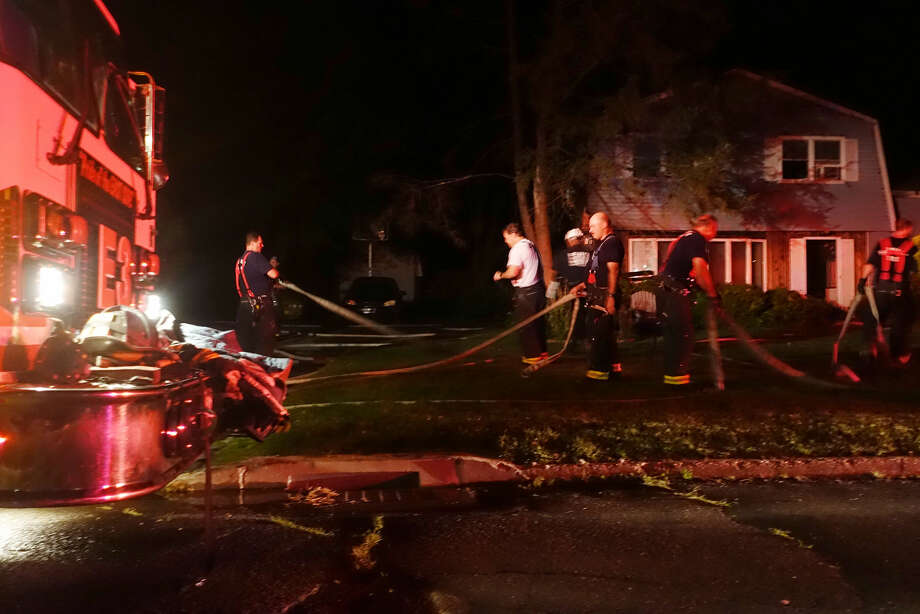 Hour photo/Jeff DaleFirefighters clean up the scene at 8 Lighthouse Lane in Norwalk Friday night after a house fire displaced a family of three and their pet bulldog Rex.