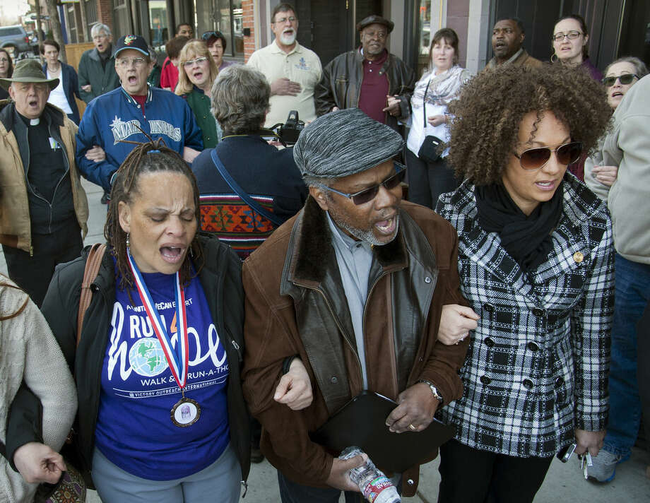 "FILE - In this Friday, March 6, 2015, file photo, from left, Della Montgomery-Riggins, Charles Thornton and Spokane NAACP president Rachel Dolezal link arms and sing ""We Shall Overcome"" at a rally in downtown Spokane, Wash., responding to a racist and threatening package received by Dolezal. Dolezal is now facing questions about whether she lied about her racial identity, with her family saying she is white but has portrayed herself as black. (Dan Pelle/The Spokesman-Review via AP, File)"