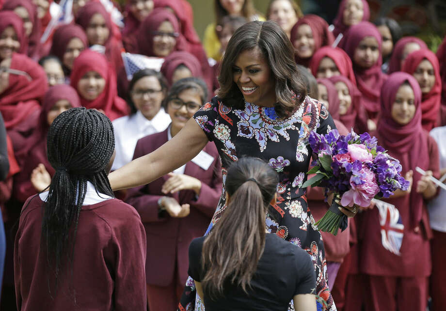 U.S. first lady Michelle Obama is greeted by pupils at Mulberry School for Girls in east London, Tuesday, June 16, 2015. Michelle Obama is due to meet with female students in London on Tuesday to encourage them to pursue top educational goals. (AP Photo/Matt Dunham)