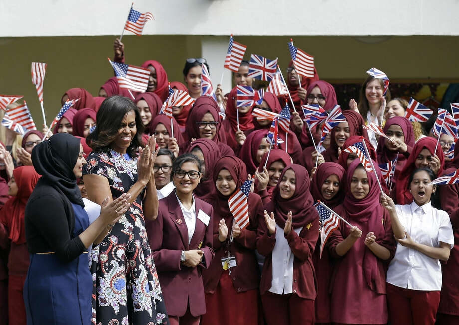 U.S. first lady Michelle Obama is greeted by pupils as she arrives at Mulberry School for Girls in east London, Tuesday, June 16, 2015. Michelle Obama is due to meet with female students in London on Tuesday to encourage them to pursue top educational goals. (AP Photo/Matt Dunham)