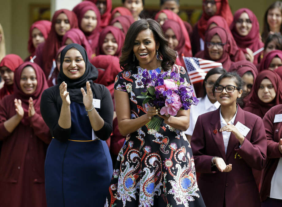 U.S. first lady Michelle Obama is greeted by pupils and teachers at Mulberry School for Girls in east London, Tuesday, June 16, 2015. Michelle Obama is due to meet with female students in London on Tuesday to encourage them to pursue top educational goals. (AP Photo/Matt Dunham)
