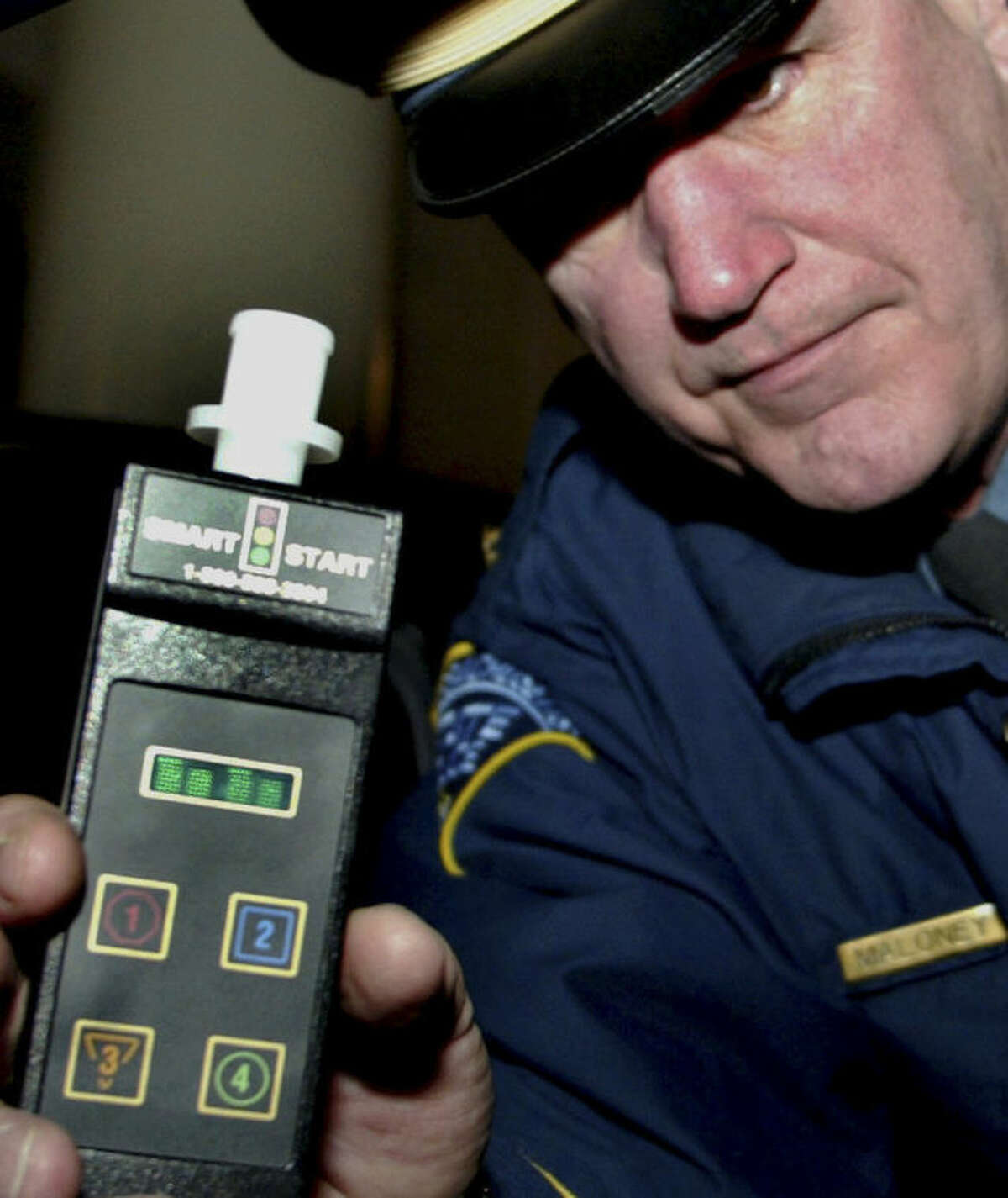 FILE - In this Jan. 3, 2006 file photo, Massachusetts State Police Lt. Paul Maloney holds an ignition interlock device outside Boston's State House. In Massachusetts, repeat drunk drivers are required to have them installed on their vehicles upon issuance of a hardship license or at full license reinstatement. In Connecticut, a measure passed unanimously by the state?'s General Assembly in spring 2014 requires first-time offenders charged with drunken driving to install similar blood-alcohol testers in their vehicles, even if they?'ve never been convicted. The bill is awaiting the signature of Connecticut Gov. Dannel P. Malloy, who has not yet received the legislation. (AP Photo/Bizuayehu Tesfaye, File)