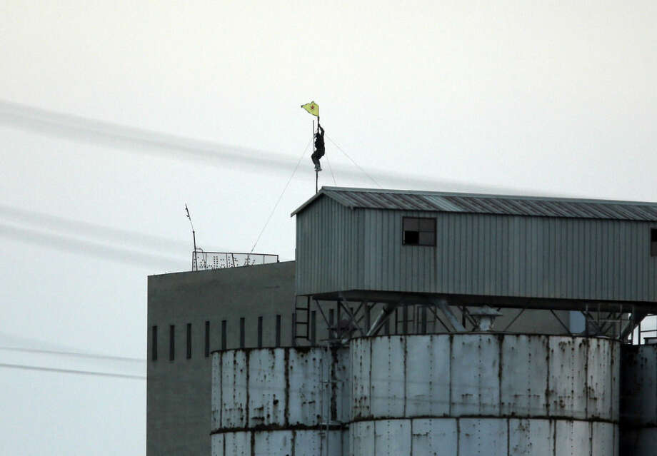 In this photo taken from the Turkish side of the border between Turkey and Syria, in Akcakale, southeastern Turkey, a Kurdish fighter with the Kurdish People's Protection Units, or YPG, climbs to install the group's yellow triangular flag on a factory in the outskirts of Tal Abyad, Syria, Monday, June 15, 2015.Kurdish fighters captured large parts of the strategic border town of Tal Abyad from the Islamic State group Monday, dealing a huge blow to the group which lost a key supply line for its nearby de facto capital of Raqqa, a spokesman for the main Kurdish fighting force said. (AP Photo/Lefteris Pitarakis)