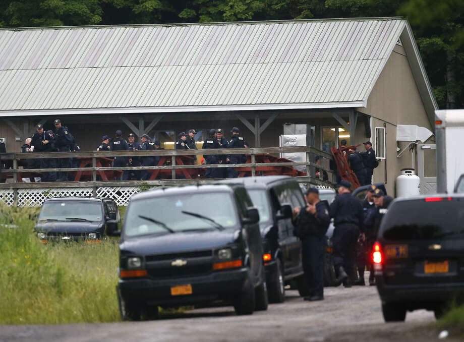 Corrections officers gather at an area near Clinton Correctional Facility before resuming the search for two escaped prisoners on Monday, June 15, 2015, in Dannemora, N.Y. Law enforcement personnel are in the tenth day of searching for David Sweat and Richard Matt, two killers who used power tools to cut their way outof the prison in Dannemora in northern New York. (AP Photo/Mike Groll)