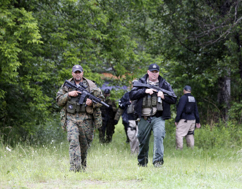 Law enforcement officers search a residential area for prison escapees David Sweat and Richard Matt, Monday, June 15, 2015, in Saranac, N.Y. Law enforcement are in the tenth day of searching for the two killers who used power tools to cut their way out of Clinton Correctional Facility in Dannemora, in northern New York. (AP Photo/Mike Groll)