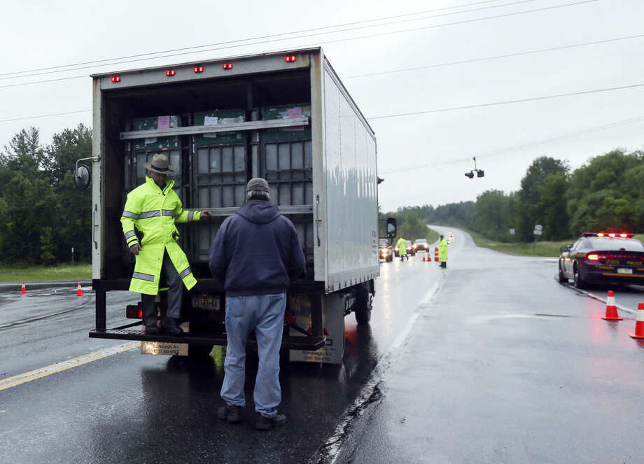 A State Police trooper checks a truck at a road block on Route 374 on Monday, June 15, 2015, in West Plattsburgh, N.Y. Law enforcement personnel are in the tenth day of searching for David Sweat and Richard Matt, two killers who used power tools to cut their way out Clinton Correctional Facility in Dannemora in northern New York. (AP Photo/Mike Groll)