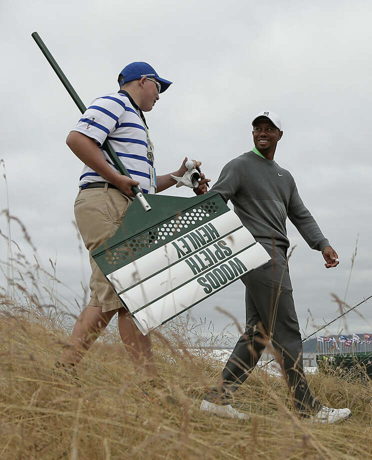 Tiger Woods signs a glove for a volunteer after a practice round for the U.S. Open golf tournament at Chambers Bay on Tuesday, June 16, 2015 in University Place, Wash. (AP Photo/Charlie Riedel)